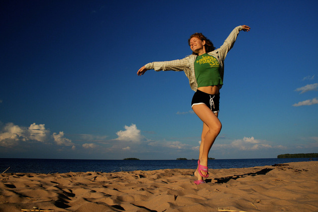Žena v krátkych šortkách a mikine pózuje na pláži.jpg