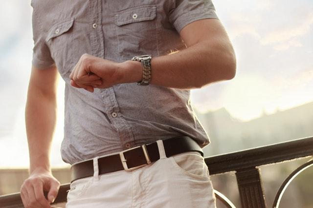Muž v hnedej košeli pozerá na hodinky na zápästí.jpg