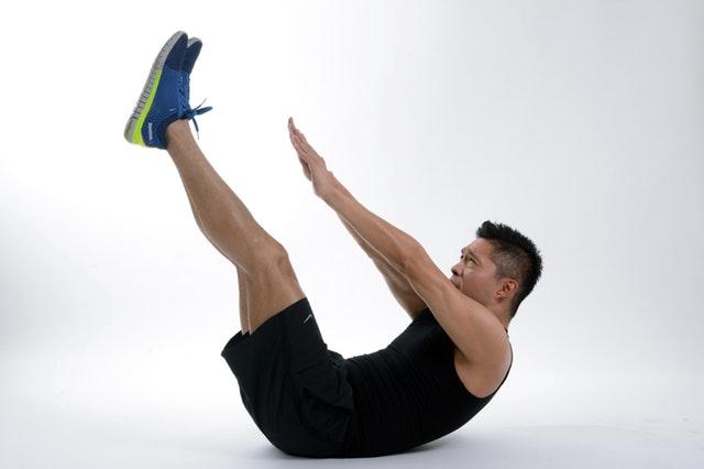 Muž v športovom oblečení, ktorý cvičí brucho