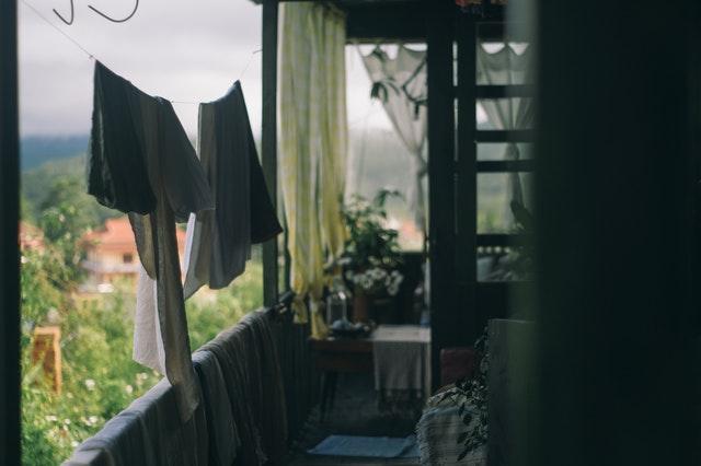 Balkón, na ktorom sú prevesené deky cez zábradlie a na šnúre visí oblečenie