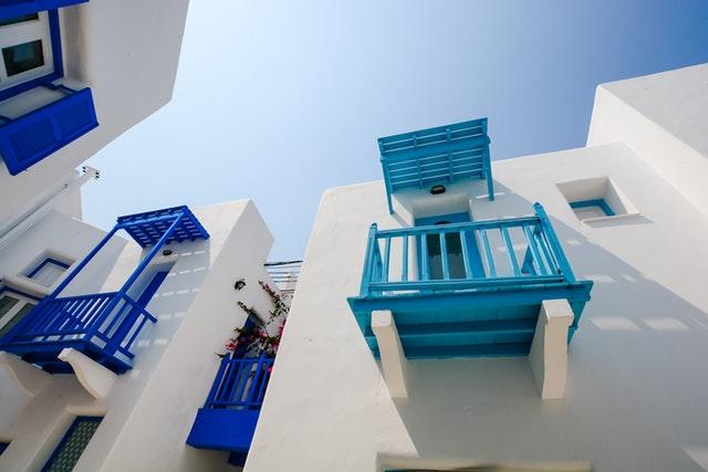 Biela budova s malými balkónmi v modrej farbe