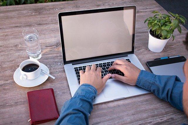 Muž sedí pri počítači s bielou obrazovkou.jpg