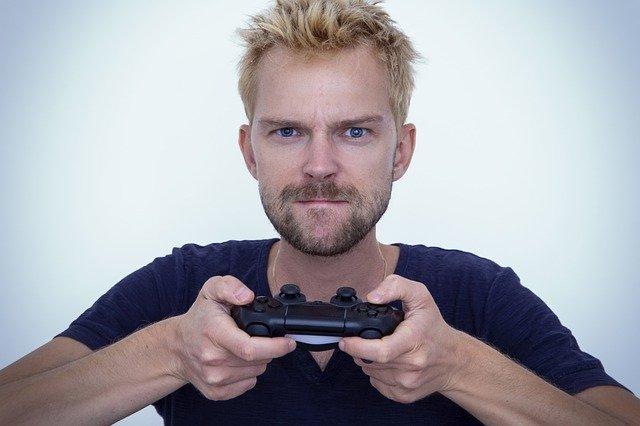 Hráč drží PS4 ovládač.jpg