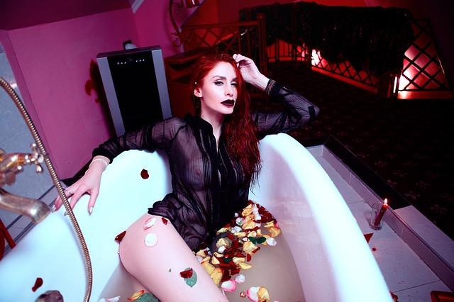 Žena v čiernej priesvitnej blúzke vo vani s vodou
