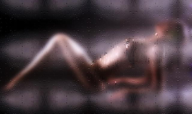 Silueta nahej ženy za sklom oroseným vodou